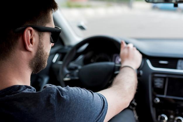 Conductor con gafas de sol con volante Foto gratis