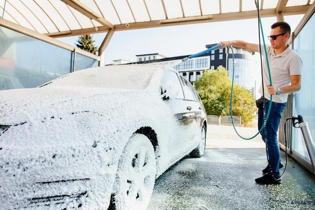 Conductor limpiando su auto con espuma de jabón Foto Premium