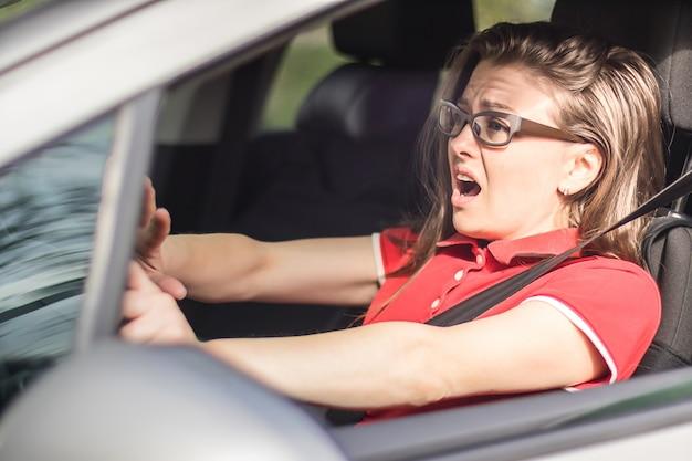 Conductora asustada tocando la bocina para evitar accidentes de tráfico Foto Premium