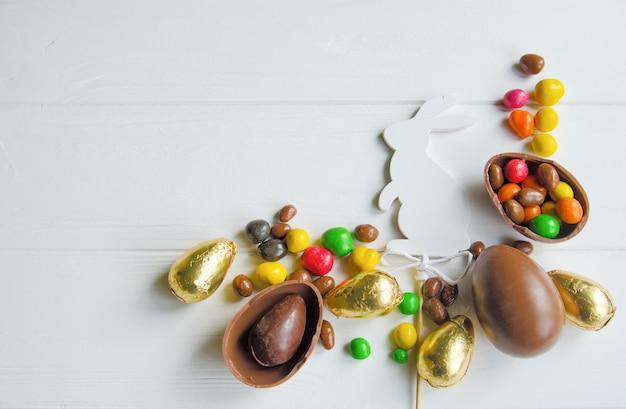 Conejito de pascua blanco con huevos de chocolate y dulces en madera blanca Foto Premium