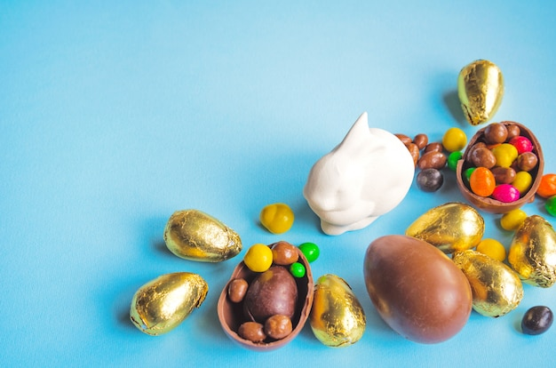 Conejito de pascua blanco con huevos de chocolate envueltos en papel dorado y dulces en azul claro Foto Premium