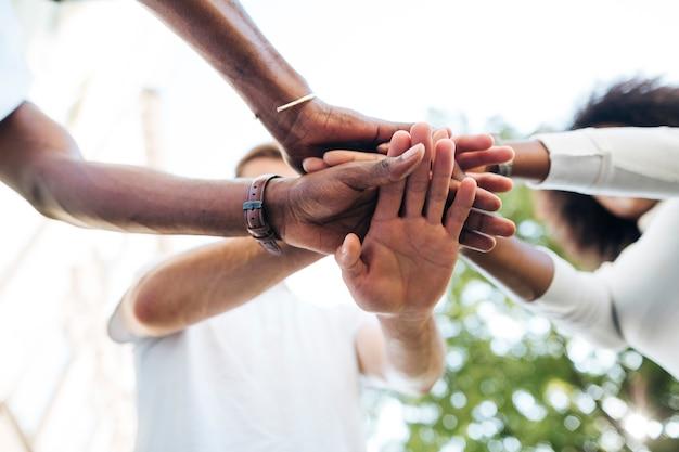 Conexión intercultural de la mano entre amigos. Foto gratis
