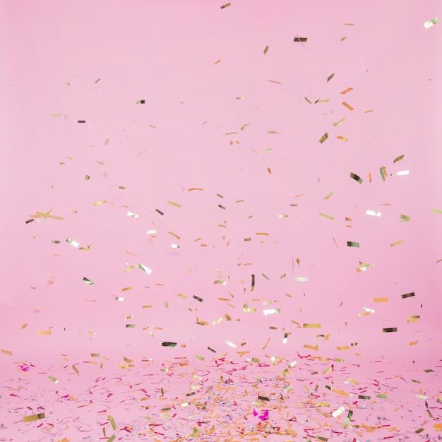 Confeti dorado cayendo sobre fondo rosa Foto gratis