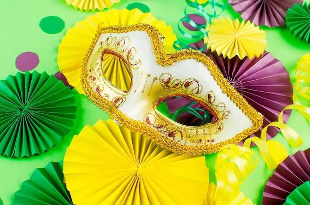 Confeti de papel de colores, máscara de carnaval y serpentina de colores sobre un fondo amarillo Foto Premium