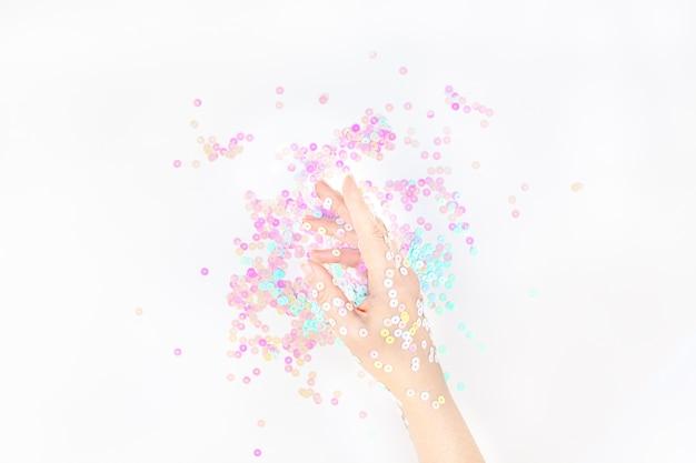 Confeti pastel perla brilla con mano de mujer Foto Premium