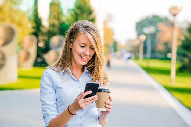 Confiantes mujeres leyendo información sobre noticias de finanzas mientras caminaba en el vestíbulo de la empresa durante el descanso del trabajo, exitosa mujer de negocios escribir mensaje de texto a su cliente mientras va con el secretario de la oficina Foto Gratis