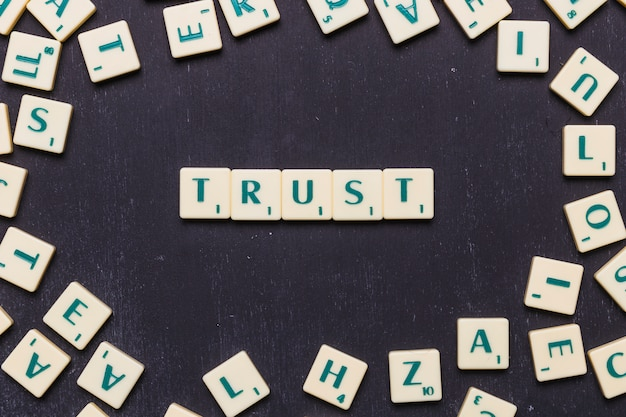 Confíe en la palabra dispuesta sobre fondo negro rodeado de letras scrabble Foto gratis