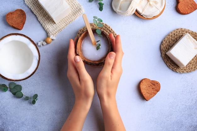 Configuración de productos cosméticos naturales con jabones y hierbas frescas vista superior manos de mujer Foto Premium