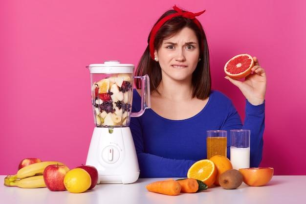 La confundida hembra emocional de cabello negro se sienta a la mesa, mordiéndose el labio, sosteniendo la mitad de la toronja en una mano, mezclando fruta en la licuadora, haciendo un batido dulce y nutritivo para una dieta saludable. Foto gratis