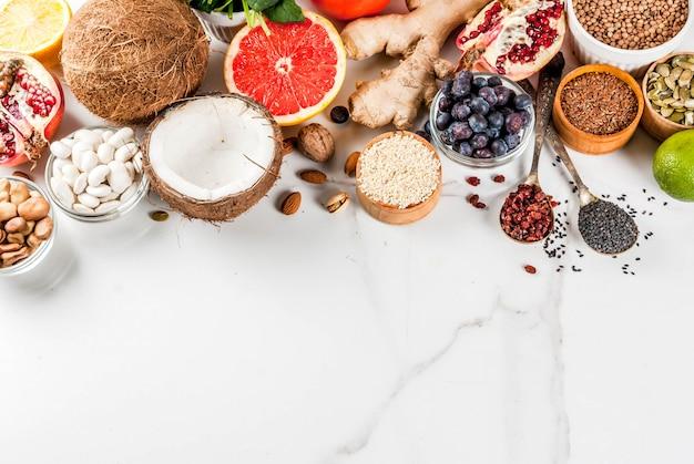 Conjunto de alimentos orgánicos de dieta saludable, superalimentos: frijoles, legumbres, nueces, semillas, verduras, frutas y verduras ... espacio de copia de fondo blanco. vista superior Foto Premium