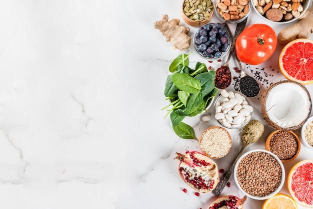 Conjunto de alimentos orgánicos de dieta saludable, superalimentos: frijoles, legumbres, nueces, semillas, verduras, frutas y verduras ... espacio de copia de fondo blanco Foto Premium