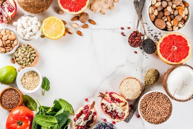 Conjunto de alimentos orgánicos de dieta saludable, superalimentos: frijoles, legumbres, nueces, semillas, verduras, frutas y verduras ... espacio de copia de superficie blanca. marco de vista superior Foto Premium