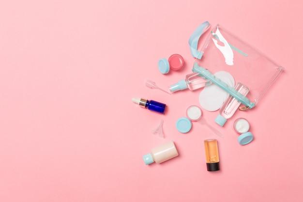 Conjunto de botellas de cosméticos de tamaño de viaje sobre fondo rosa. endecha plana de tarros de crema. vista superior del concepto de estilo de cuidado corporal Foto Premium