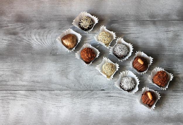 Conjunto de caramelos de chocolate. exclusivos bombones hechos a mano en mesa de madera. vista superior, copyspace Foto Premium
