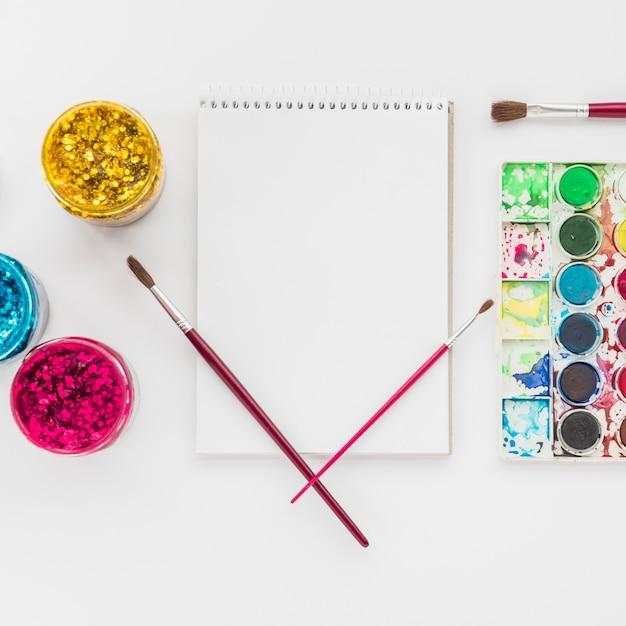 Conjunto de color de agua y brillo con bloc de notas espiral aislado sobre fondo blanco Foto gratis