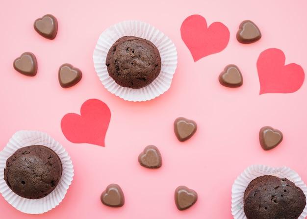 Conjunto de corazones de chocolate dulce cerca de muffins y tarjetas de san valentín Foto gratis