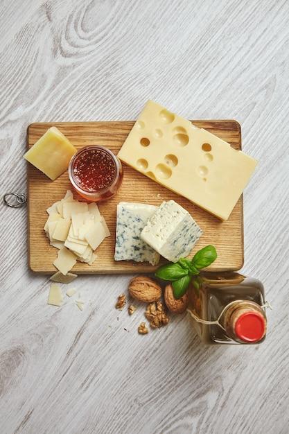 Conjunto de cuatro quesos en tabla de cortar rústica. servido para el desayuno con aceite de oliva virgen extra en botella vintage, miel rústica y nueces con hojas de albahaca Foto gratis