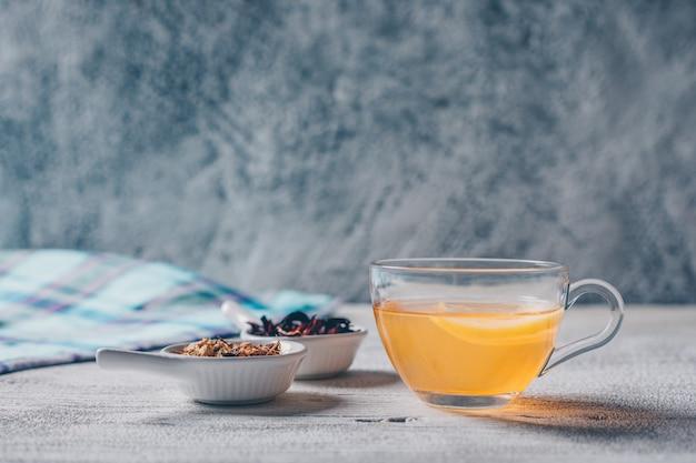 Conjunto de hierbas de té y agua de color naranja sobre un fondo gris. vista lateral. Foto gratis
