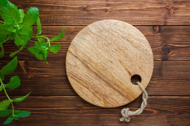 Conjunto de hojas y tabla de cortar sobre un fondo de madera. vista superior. copiar espacio para texto Foto gratis