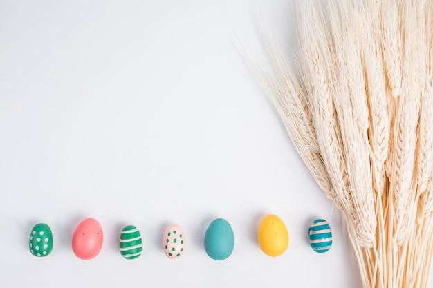 Conjunto de huevos de pascua brillantes cerca de manojo de trigo Foto gratis
