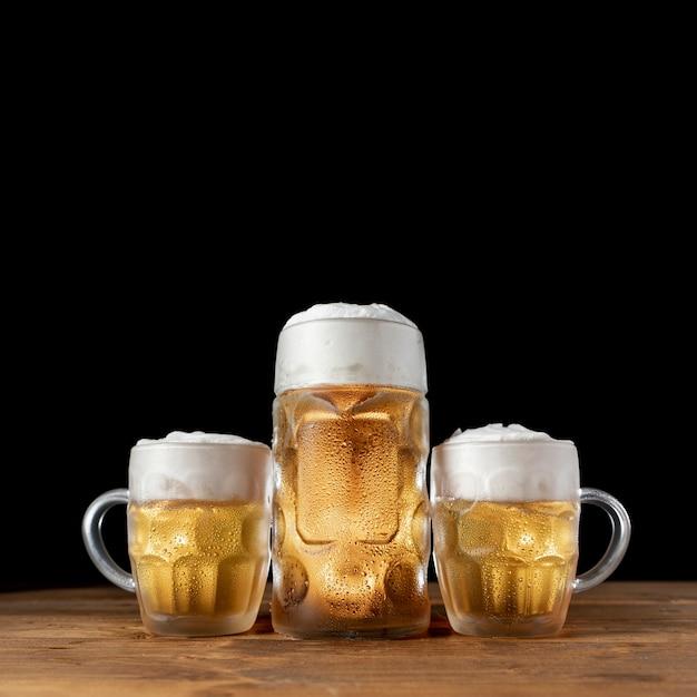 Conjunto de jarras de cerveza en una mesa de madera Foto Premium