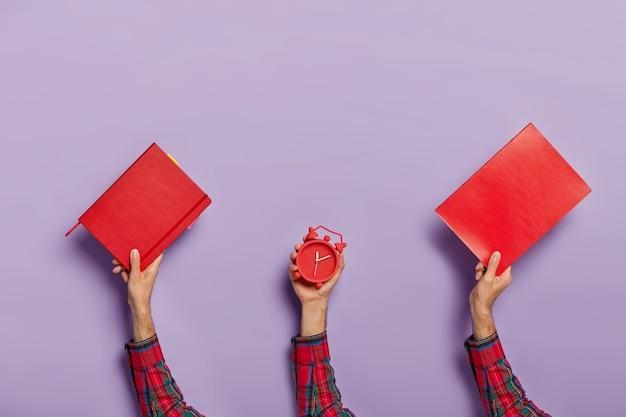 Conjunto de manos masculinas llevan bloc de notas rojo, libro de texto y despertador Foto gratis