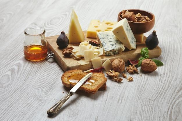 Conjunto de quesos en tabla de cortar rústica aislado en el lado de la mesa de madera blanca cepillada, servido para un delicioso desayuno con higos, miel rústica, pan seco y nueces en un tazón con hojas de albahaca Foto gratis