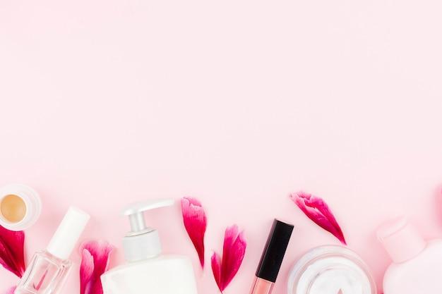 Conjunto rosa de productos cosméticos y pétalos Foto gratis