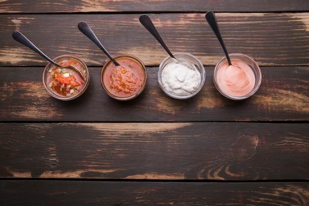 Conjunto de salsas en cuencos con cucharas. Foto gratis