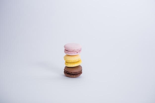 Conjunto de tres macarons en el espacio en blanco con espacio de copia. los macarrones marrones, amarillos y rosados están en una fila. Foto Premium