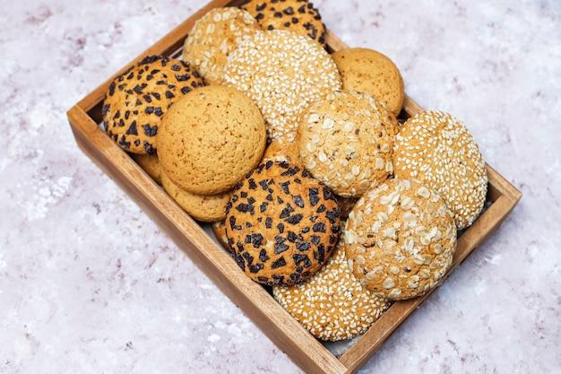 Conjunto de varias galletas de estilo americano en bandeja de madera sobre fondo de hormigón ligero. galletas de mantequilla con semillas de sésamo, mantequilla de maní, avena y galletas de chispas de chocolate. Foto gratis