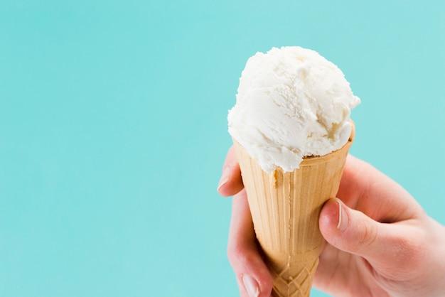 Cono de helado de vainilla blanco en la mano Foto gratis
