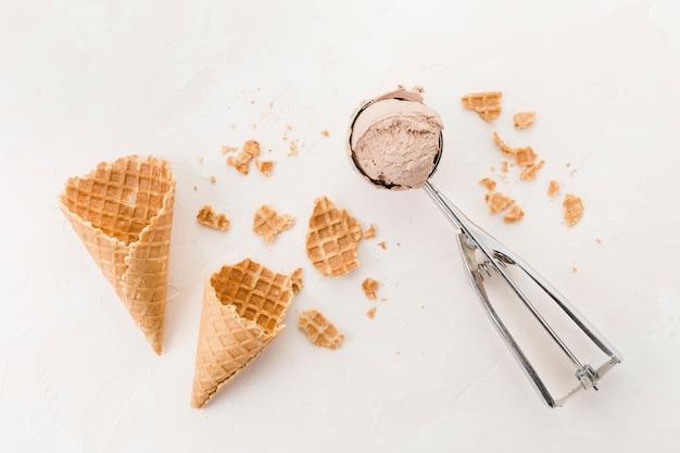 Conos de galleta crujientes y helado sobre fondo claro Foto gratis