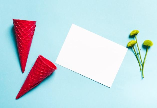 Conos de galleta y hoja de papel sobre fondo claro Foto gratis