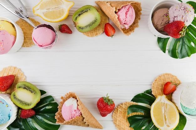 Conos de helado, frutas y hojas verdes. Foto gratis