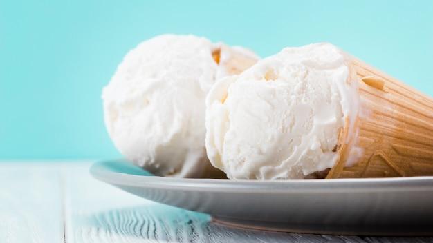 Conos de helado de vainilla deliciosos que ponen en la placa Foto gratis
