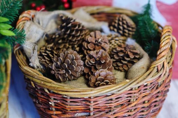 Conos de pino en una cesta. decoración navideña Foto Premium