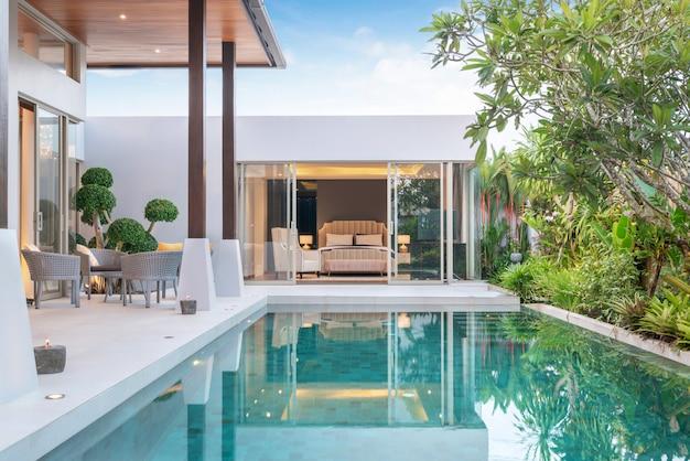 Construcción de casas o casas diseño exterior e interior que muestra una villa con piscina tropical con jardín verde y dormitorio Foto Premium