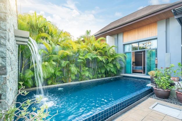 Construcción de casas o casas diseño exterior e interior que muestra una villa con piscina tropical con jardín verde Foto Premium