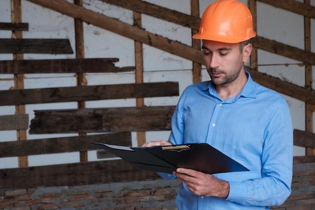Constructor de edificios arquitecto ingeniero con casco naranja Foto Premium
