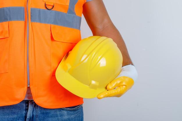 Constructor masculino en uniforme, jeans, guantes con casco en la mano, vista frontal. Foto gratis