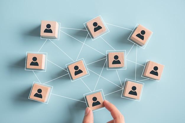 Construyendo un equipo fuerte, bloques de madera con icono de personas sobre fondo azul, recursos humanos y concepto de gestión. Foto Premium