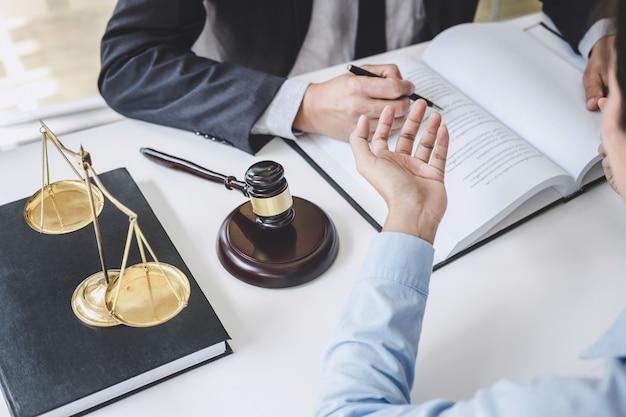 Consulta y conferencia de abogados de sexo masculino y empresaria profesional que trabaja y debate en un bufete de abogados en el cargo. conceptos de ley, juez de martillo con escalas de justicia. Foto Premium