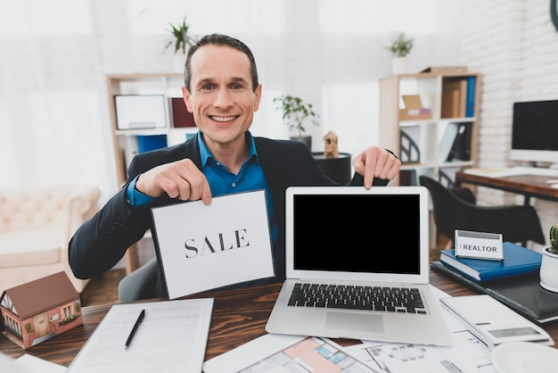 Consultor feliz con laptop real estate office. Foto Premium