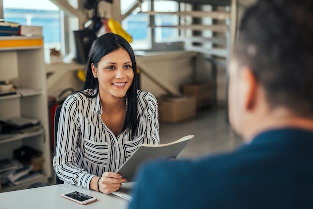 Consultor de la mujer que habla con el cliente en oficina. Foto Premium