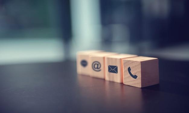 Contáctenos concepto, teléfono con símbolo de bloque de madera, correo y dirección en el escritorio. Foto Premium