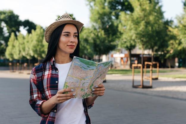 Contemplando a joven sonriente con mapa en la calle Foto gratis