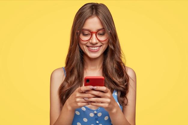 Contenido adolescente con cabello largo, sostiene un teléfono celular moderno, se desplaza por las redes sociales, tiene una expresión alegre Foto gratis