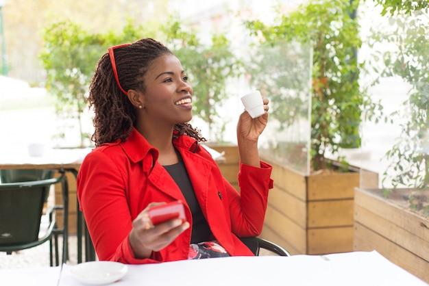 Contenido mujer tomando café y usando el teléfono inteligente Foto gratis