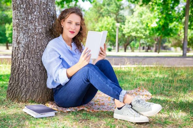 Contenido, niña bonita, lectura, libro de texto, en el estacionamiento Foto gratis